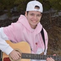 Demetra in a pink and white sweatshirt and backwards white hat