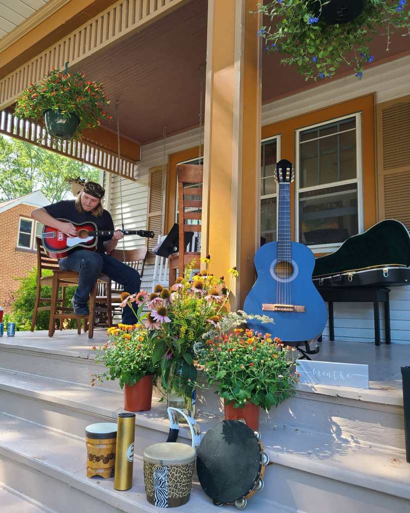 Musiician playing on a large porch in Grafton