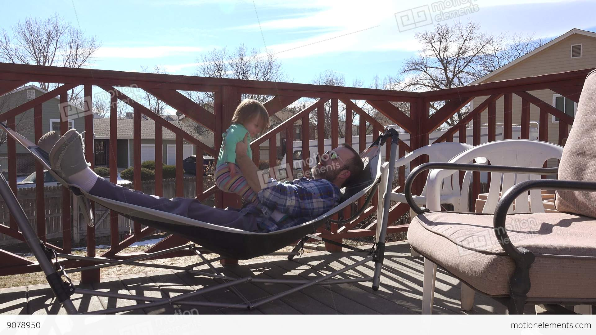 Dad Playing With Toddler On Outdoor Deck Hammock In Summer