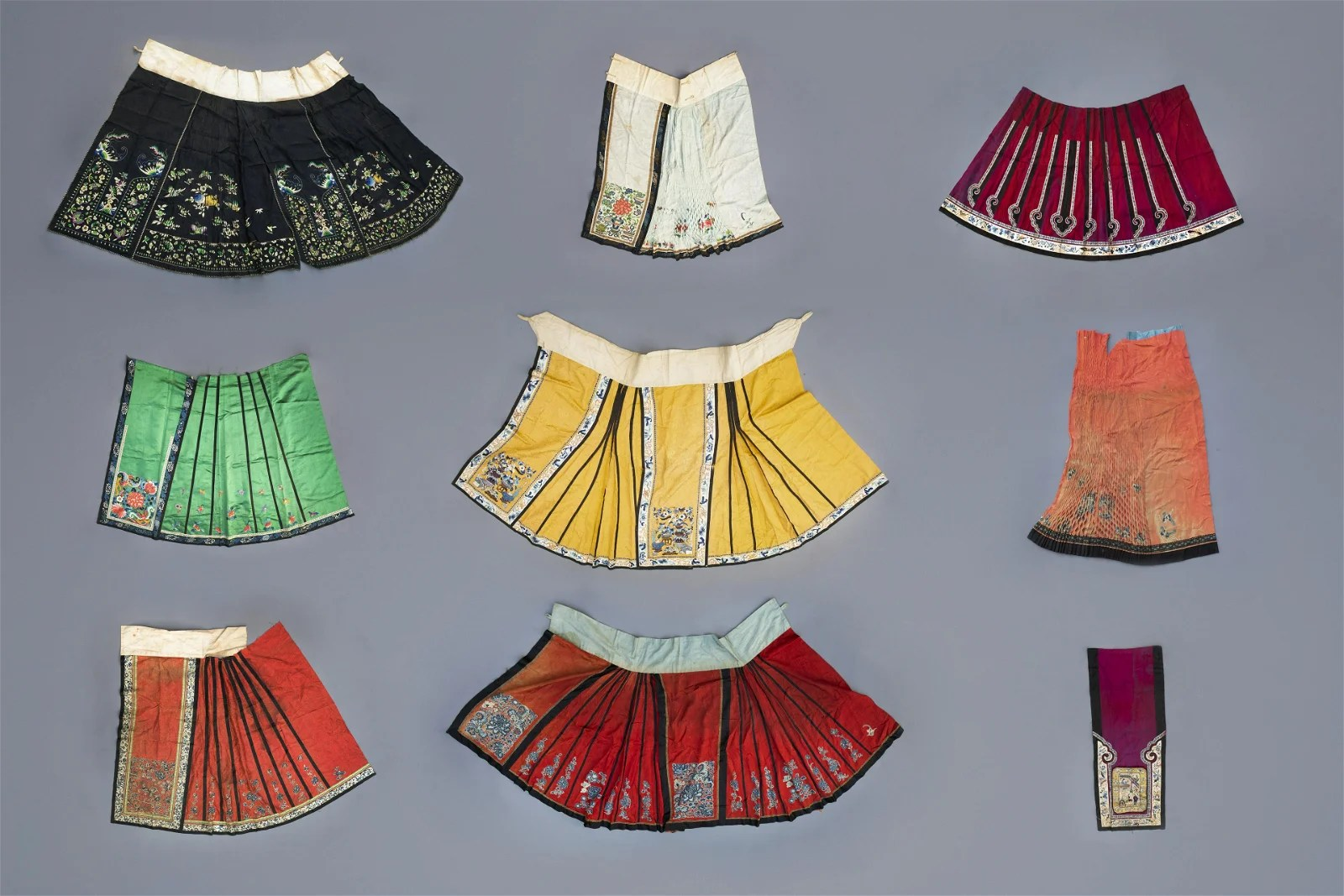 A collection of Chinese embroidered silk girls' skirts,