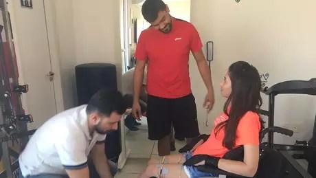 Laís começa a sessão de fisioterapia com Robson Lopes; de pé, Willian, um de seus cuidadores