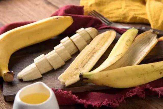 Banana fatiada ao lado da casca da fruta