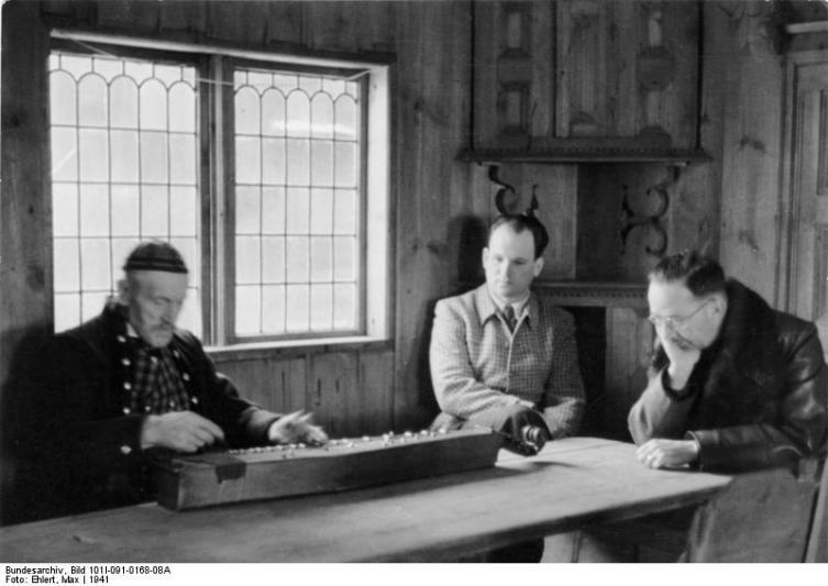 Heinrich Himmler (til høyre) lytter til folkemusikeren Ola Brenno på Norsk Folkemuseum under et av sine besøk (Foto: Wikipedia)