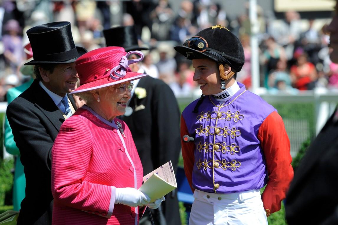 Dronning Elizabeth II, regjerende monark siden 6. februar 1952, er meget galoppkyndig. Her er hun smilende til stede på The Royal Ascot, et sentrum i engelsk galopp. I 2013 fikk den snart 89-årige monarken utmerkelsen «Årets Hesteeier» i England. William Buick har ridd flere av Dronningens hester tidligere. (Foto: George Selwyn)