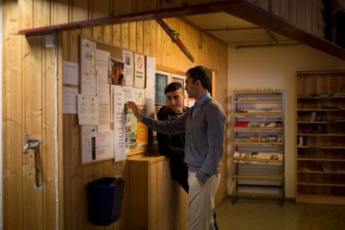 Mohsen og faren Ahmad er på kontoret til mottaket for å se om de har fått noe mer informasjon om sin nye bolig i Øyer. Når beboerne på mottaket får post skrives navnet deres opp på en gul postit-lapp som de viser for å få posten sin. (Foto: Mari Aftret Mørtvedt)