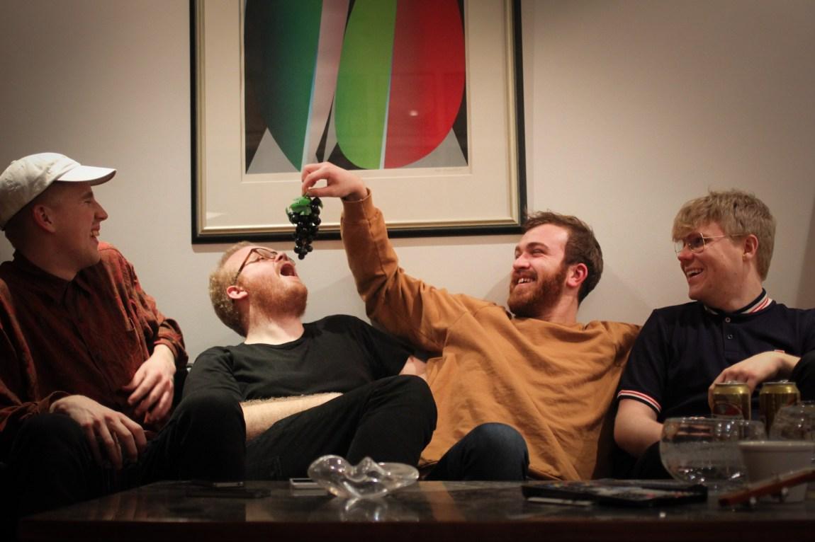 Axels kompiser Eirik (holder druer) og Peter (caps) har kjærester, mens Kim er like ettertrykkelig singel som Axel. Men i motsetning til Axel har Kim (spiser druer) et ganske skamfullt forhold til Tinder. (Foto: Frid. K Hansen)
