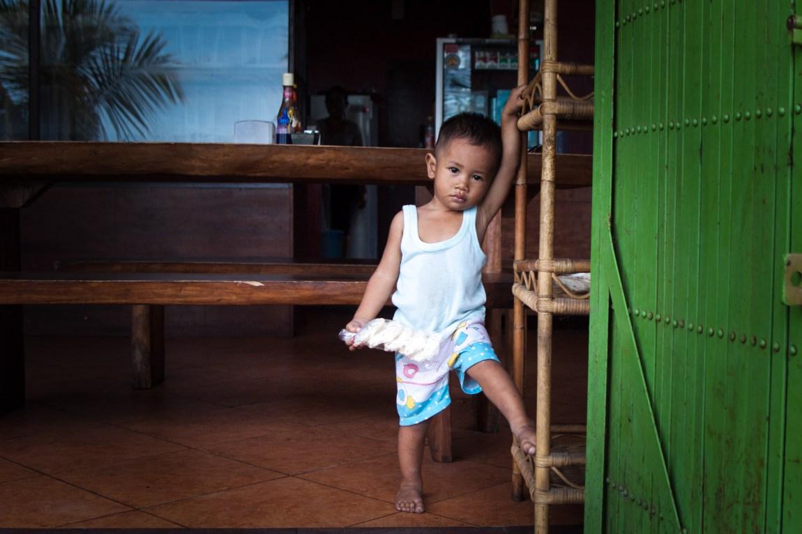 En liten gutt henger ved inngangen til en liten butikk langs veikanten.  (Foto: Andrea A. Thiis-Evensen)
