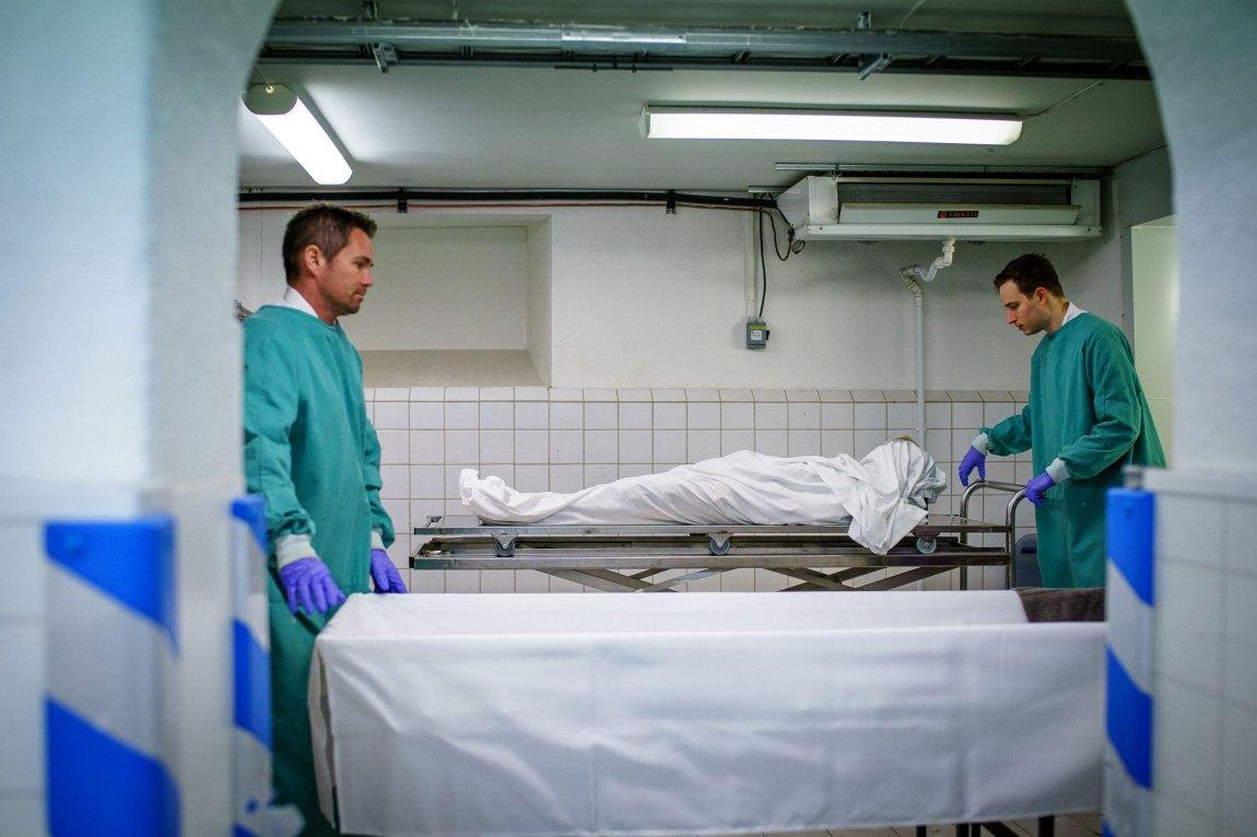 Hans Magnus hjelp av en kollega til å løfte den døde over i kista. Dette har de gjort mange ganger før.
