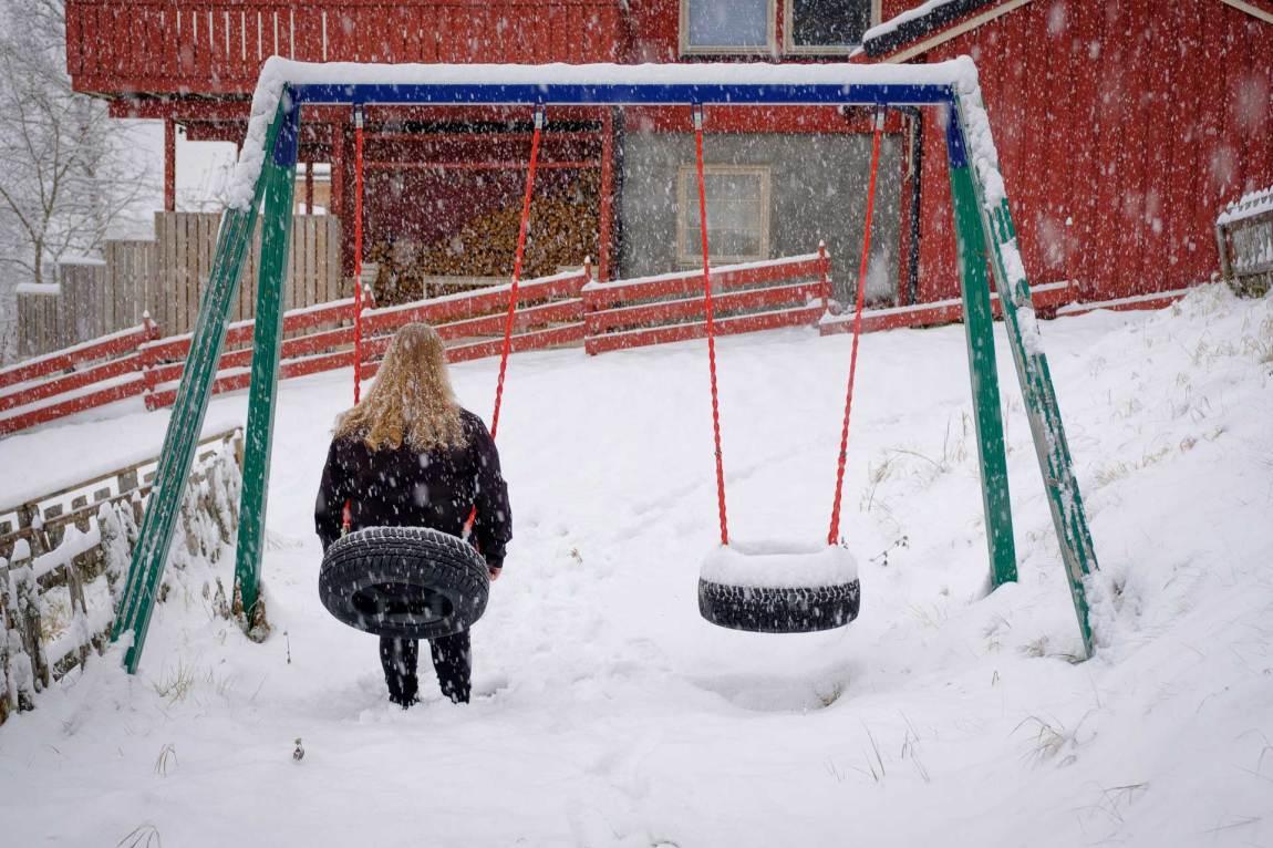 Lena sit på ei huske, det snør og ho har snøkrystaller i håret. Lena kan framleis hugse dagen då alt vart raudt. Ho satt på huska på leikeplassen. Foto: Lars Erik H. Andreassen
