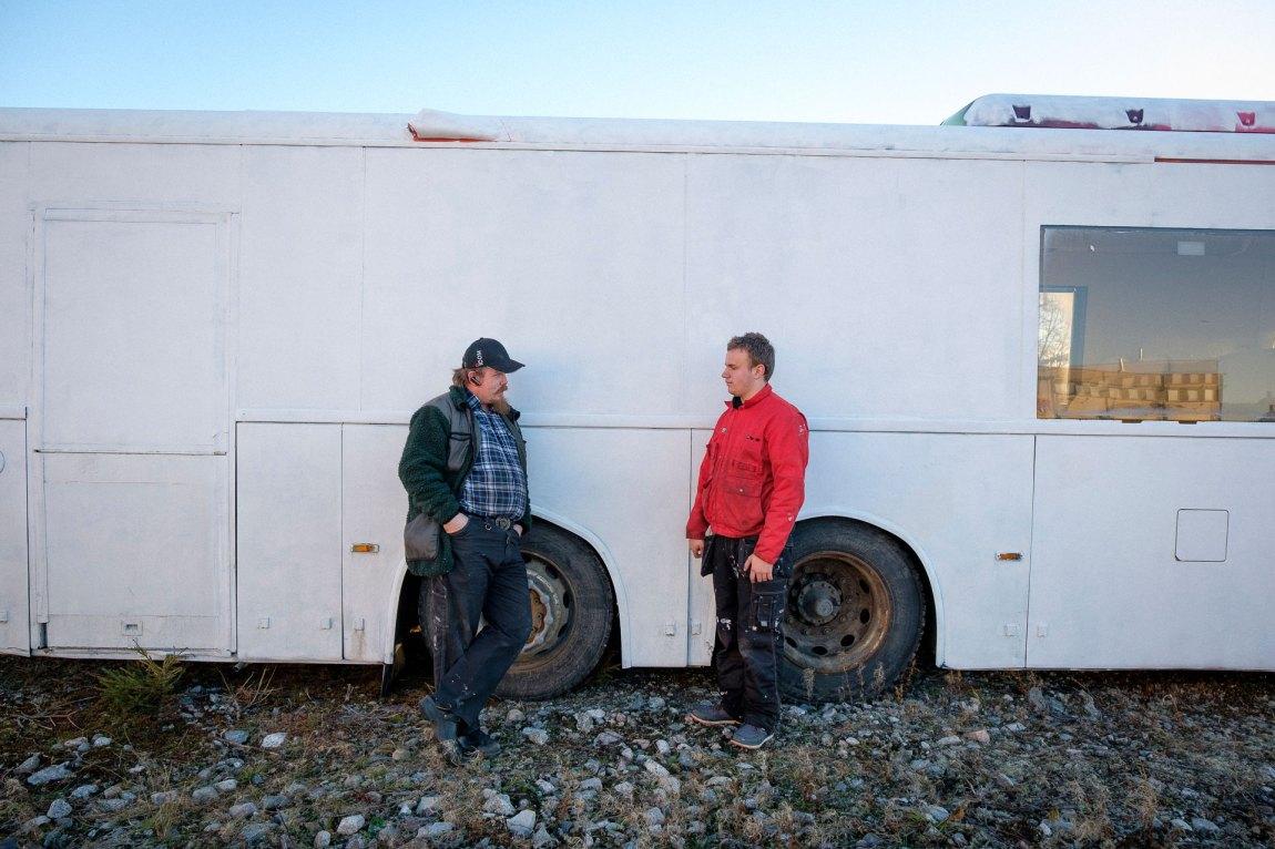 Markus og kollegaen Per Kristian lener seg mot ein kvitmåla rutebuss. Dei har arbeidsklede på. Foto: Lars Erik H. Andreassen