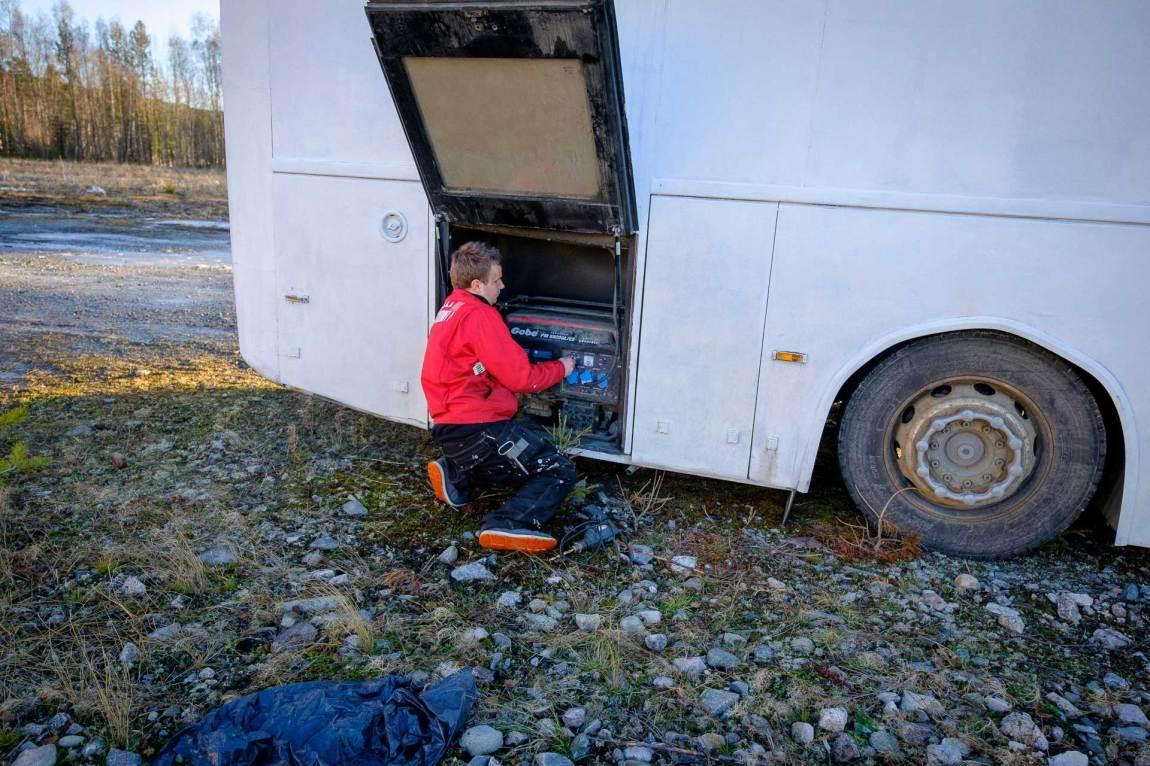 Markus lener seg inn i eit motorrom bak på ein kvitmåla buss. Han har på seg raud arbeidsjakke og svart arbeidsbukse. Markus får start på eit aggregat som fuskar litt slik at han kan få straum i bussen. Foto: Lars Erik H. Andreassen