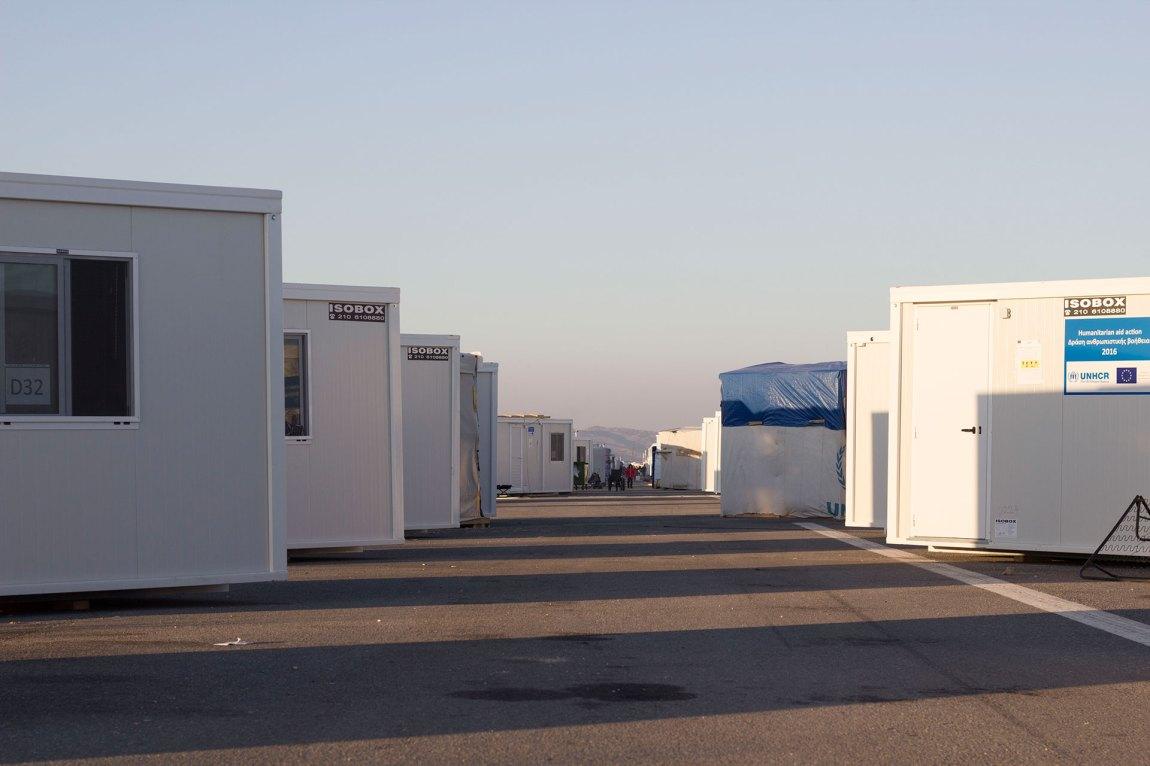 På to rekkjer står isoboksane som er heimane til nærare 700 flyktningar i Nea Kavala nedover den nedlagde flystripa. Foto: Siri Bråtveit