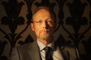 Lars Mikkelsen, framfor det karakteristiske «Sherlock»-tapetet. (Foto: BBC)