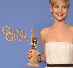 Jennifer Lawrence viser frem Golden Globe-prisen på bakrommet. (Foto: AFK / Robyn Beck)