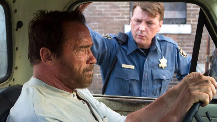 Wade (Arnold Schwarzenegger) blir spurt om datterens tilstand av politimannen Ray (Douglas M. Griffin) i Maggie (Foto: SF Norge AS).