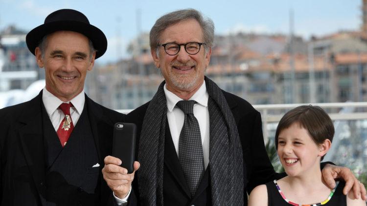 Steven Spielberg filmer (vertikalt!) med mobilen sin, med skuespillerne Mark Rylance og Ruby Barnhill ved sin side i Cannes (Foto: AFP PHOTO / ANNE-CHRISTINE POUJOULAT).