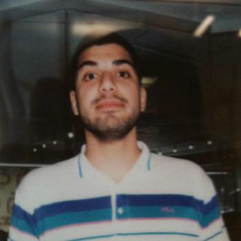 Ali ser overraska inn i kamera. Bilde er litt uklart, som om det er tatt med eit gammal analogt kamera, Han har mørkt, kort hår og litt mørke skjeggstubbar. Han har på seg ein kvit gensar med blå striper.