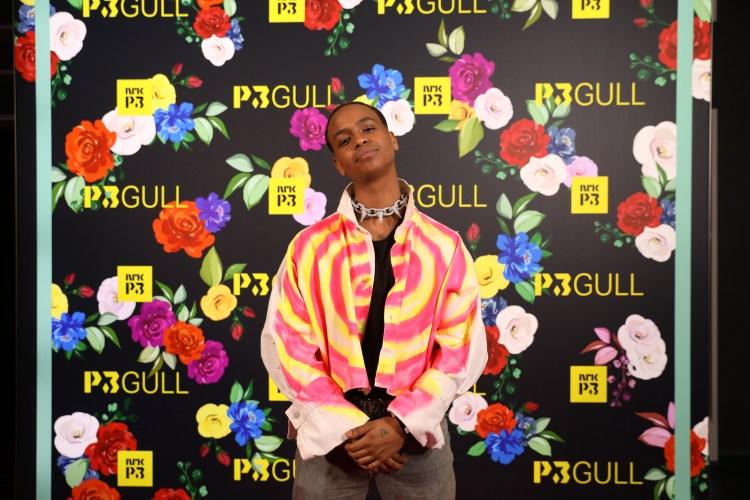 Isah står med hendene foldet og ser rett inn i kamera. Han har på en rosa og gul bluse, og et piggete halsbånd.