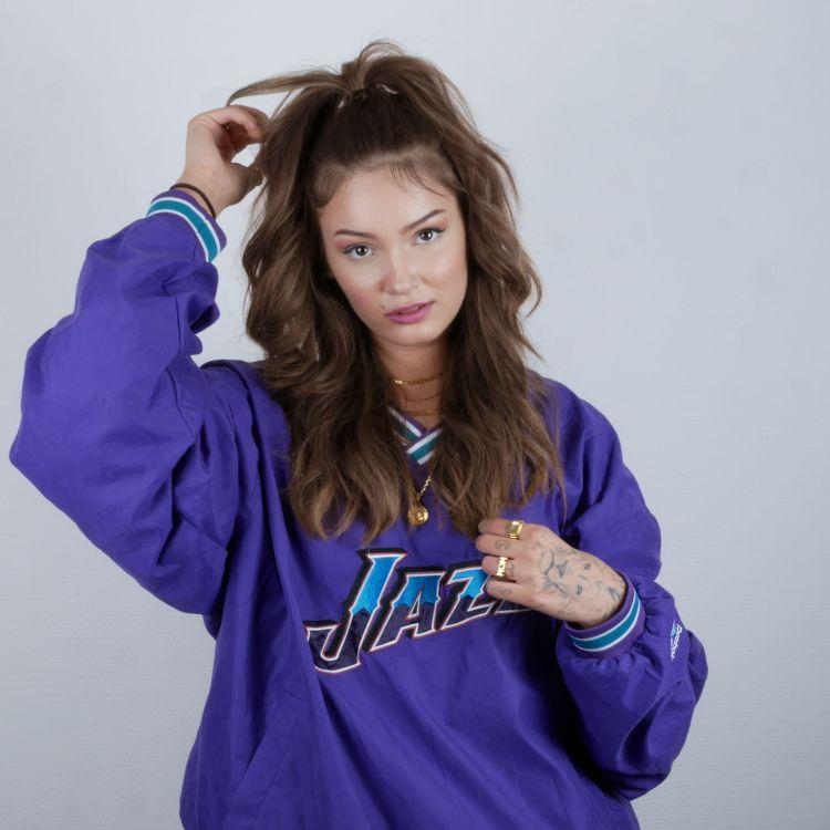Isabell har på seg ei oversized lilla jakke. Håret er satt opp i 80-tals-stil. Ho ser alvorleg inn i kamera medan ho tek seg til håret.