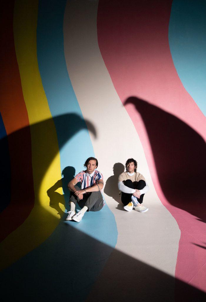 De to medlemmene i bandet sitter på gulvet i et rom som er malt stripete i gul, rød, blå, beige og rosa. Skygger kaster seg opp etter veggene og de to stirrer tomt ut i rommet.