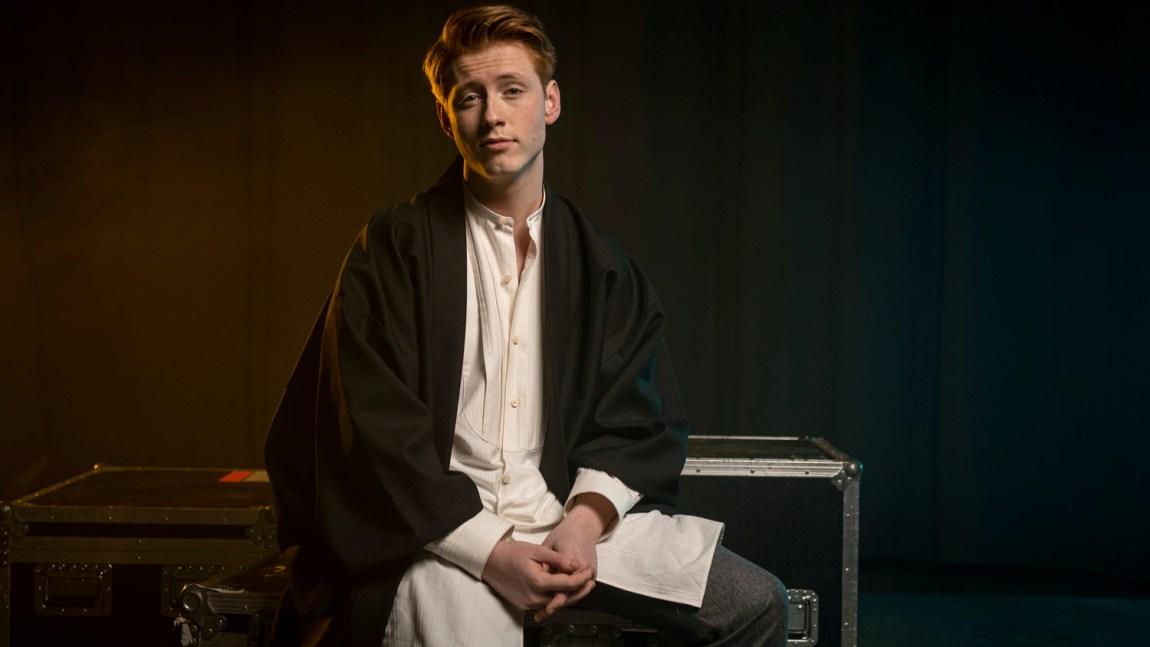 Bjarte de Presno Borthen sitter på en benk i et studio og ser rett i kamera. Han har hvit, lang skjorte på og sort jakke over. Bildet er et pressfoto til tv-programmet De neste.