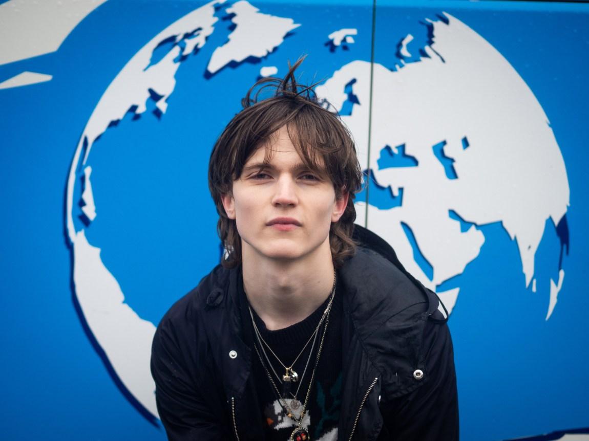 Et bilde av Simon som ser inn i kamera. Bak hodet hans er en grafikk med en jordklode, på en turistbuss.