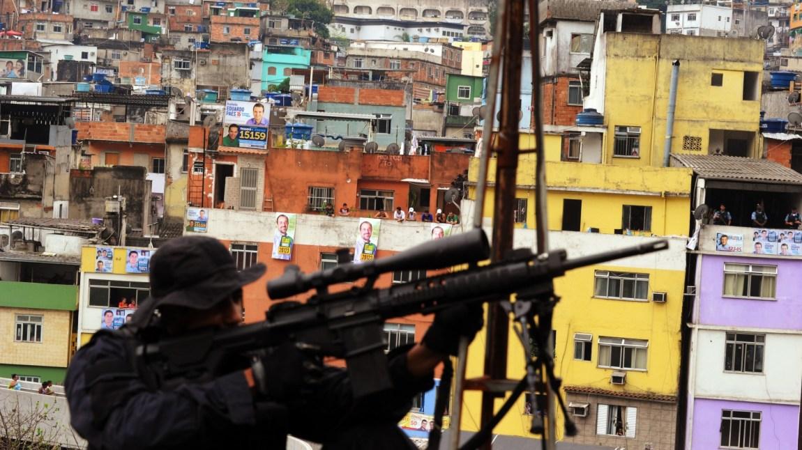 En brasiliansk politi-skarpskytter i Rocinha-favelaen i Rio de Janeiro. Brasilianske myndigheter rykket inn med politistyrker i september 2012, i håp om å pasifisere favelaen. (Foto: NTB Scanpix, Antonio Scorza)