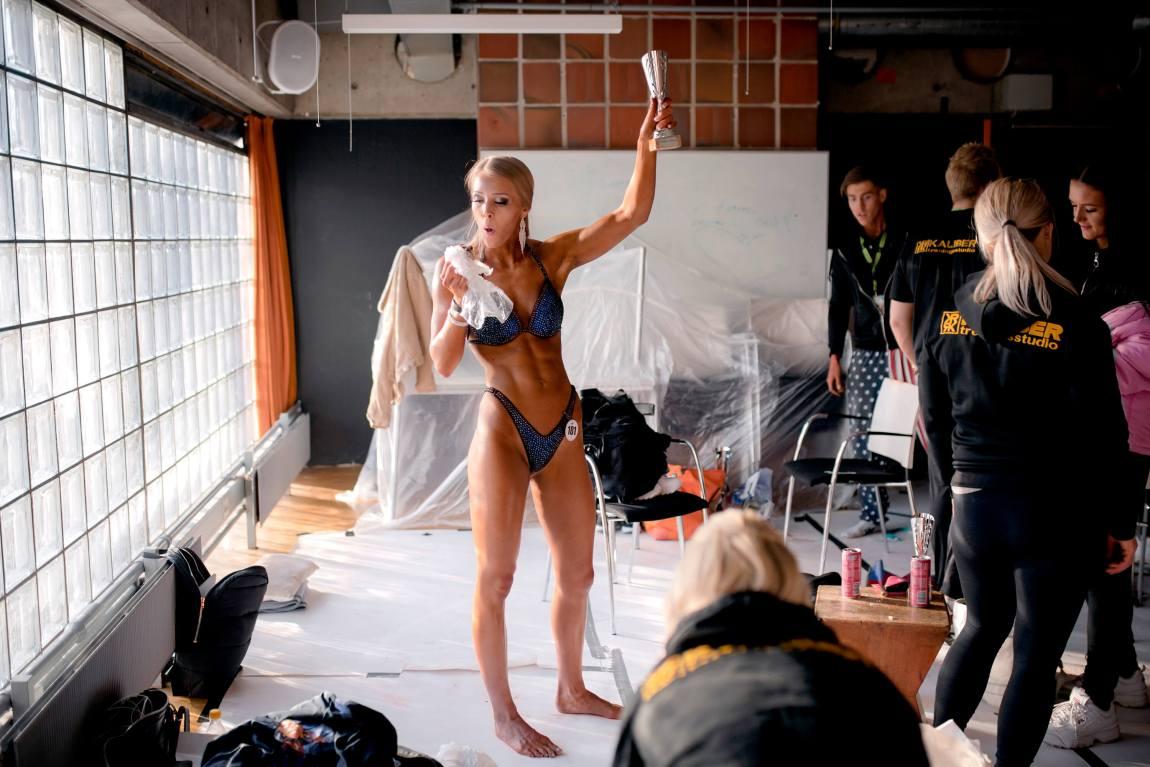 Med en donut i den ene og pokalen i den andre står Tonje i bikini på bakrommet. Blikket er festet på donuten hun nettopp har tatt en enorm bit av.