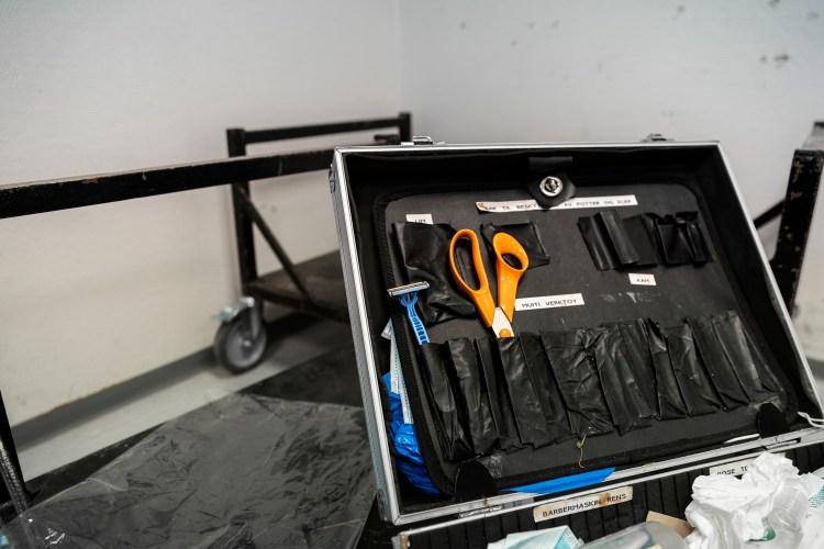 På to sorte paler står en håndtverkskoffert. Kofferten er åpen, med sort stoffmateriale inni. Inni kofferten henger sorte lommer, med en blå barberhøvel og oransje saks.