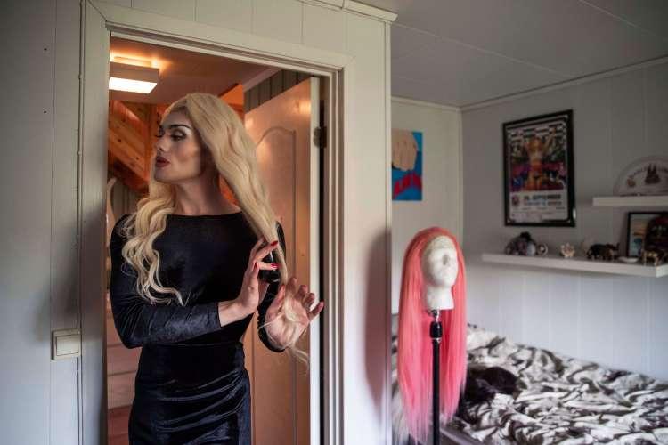 Sondre står i døråpningen og drar i de  blonde parykken på sin venstre side. Han tittemot venstre ut av bilderamen. Bak han står stativet med den rosa parykken.
