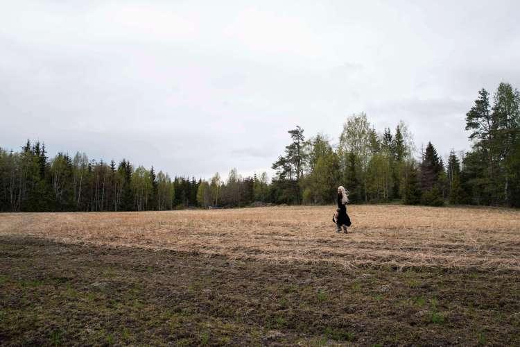 Et stort jorde, hvor det ser ut til at kornene er høstet. Bak jordet er furuskog. Sondre løper over jordet i den sorte kjolen, og ser seg bakover til kamera.