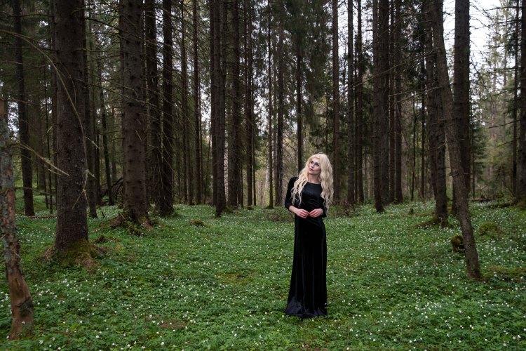 Sondre omkranset av høye trær, grønt gress og hvitveis. Han står til høyre i bildet i lang sort kjole og titter opp mot sin høyre med et alvorlig ansiktsuttrykk. Hendene foldes foran han.