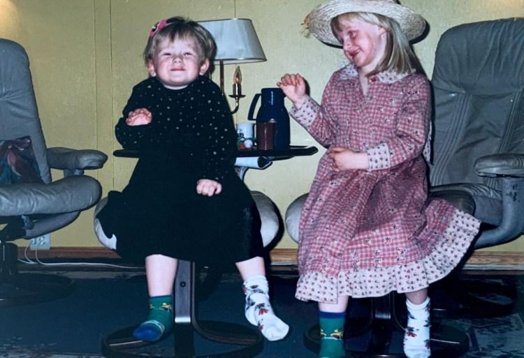Gammedags bilde, tatt med et analogt kamera. Sondre er barn, og sitter til venstre og smiler til kamera i sort kjole med blomster på. Til høyre sitter søsteren med stråhatt og rød kjole, smilende mens hun ser på Sondre.