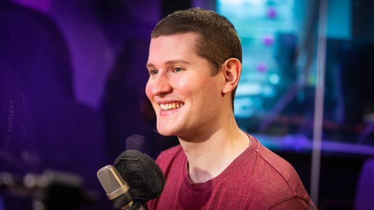 Henrik Farley sitter foran mikrofonen i et radiostudio og smiler.