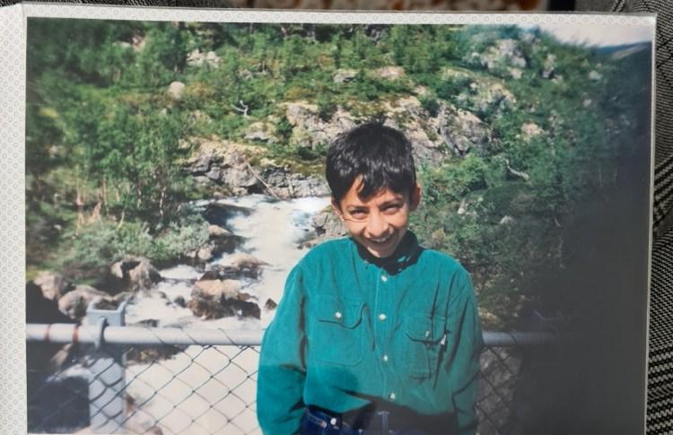 Bildet viser eit bilete i eit fotoalbum frå då Waleed var yngre. Han står framfor ein foss, og smilar beskjedent inn i kamera.