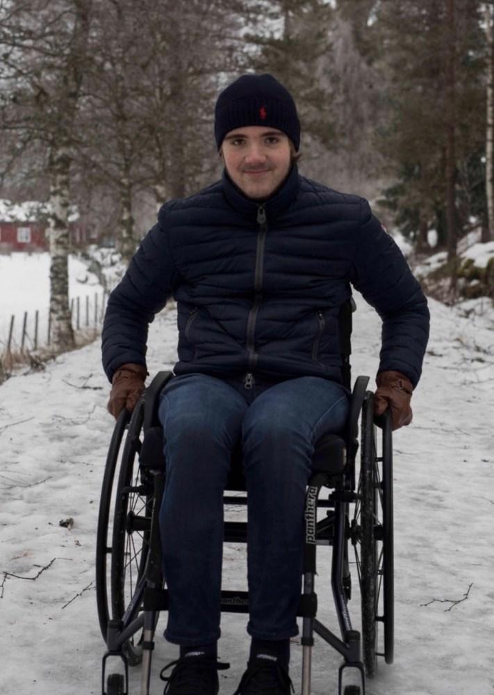 Marcus smiler til kamera. Han held fast i hjula på rullestolen. Det er eit tynt lag med snø på bakken rundt han.