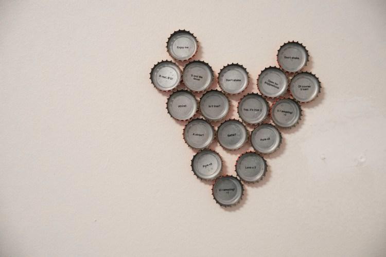 På den hvite veggen til Synne henger det Cola-corker som former et hjerte. Det er toppen av krokene som er limt på veggen, slik at den metalliske innsiden synes. På innsiden av korkene står det ulike ord i sort skrift. Det står blant annet  «Love U 2» og  «U r amazing».