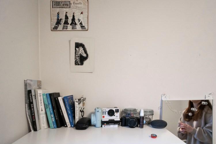 Rommet til Synne med hvit vegg og hvit kommode. På veggen over kommoden henger et bandbilde av The Beatles som går over et fotgjengerfelt. Under henger en tegning av en giraff som venninnen hennes tegnet på folkehøyskole. På toppen av kommoden er det stilt opp bøker og notatbøker. Ved siden står et Polaroid-kamera, et Fuji-kamera og et digitalt Sony-kamera. Til høyre er et speil med lyslenker, hvor vi kan se Synnes refleksjon.