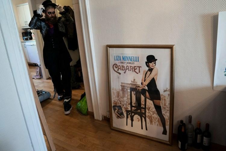 Til Venstre står Åshild i fullt kostyme: dress, hansker, hatt og skjegg. Hun står i gangen og retter på hatten mens hun ser seg i speilet. Til høyre i bildet skimtes inngangen til soverommet, hvor en stor filmplakat som er rammet inn lener seg på gulvet og veggen. På plakaten er det reklame for den ikoniske filmen «Cabaret» med showgirl Liza Minelli. Hun har på sort kjole, sorte sko og sort bowlerhatt.