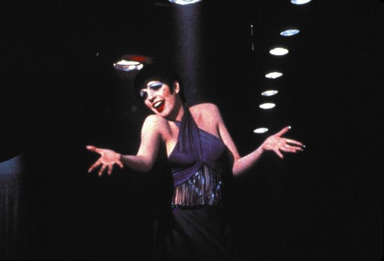 Bilde av den kjente skuespilleren Sally Bowels, med sort kort hår, mye sminke, lilla singlet og et stort smil. Armene er utslått, og det ser ut som hun holder et sceneshow.
