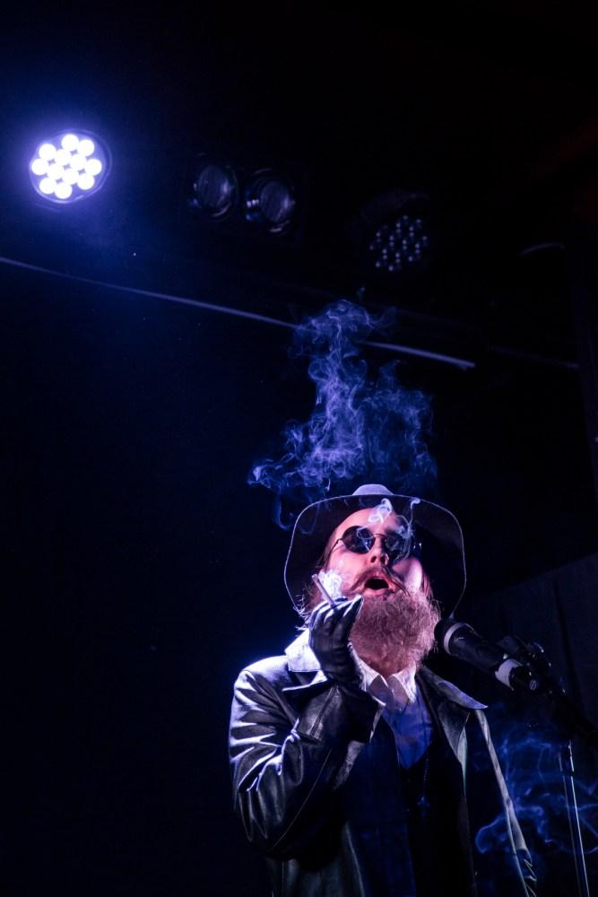 Åshild står på en mørk scene med blått scenelys. Hun holder en sigarett i hånda og har nettopp tatt et drag, slik at røyken fyller rommet og munnen hennes er halvåpen. Hun har på sort skinnjakke, hvit skjorte, sort hatt og runde solbriller.