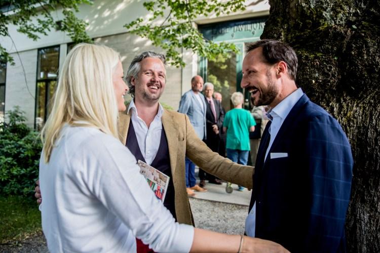 Mette-Marit, Ari Behn og Håkon står i ein sirkel. Dei snakker saman og ler. Det er ein flott sommardag, og i bakgrunnen ser ein galleriet som har utstilling.