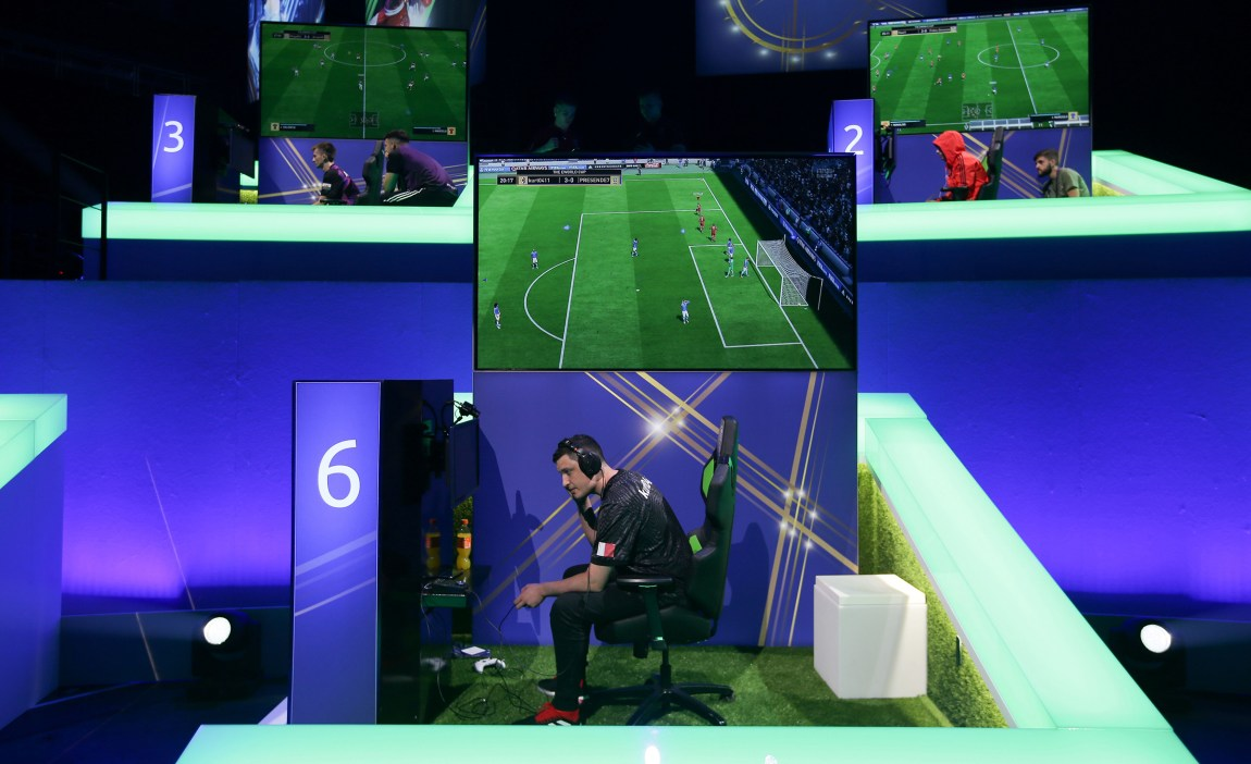 En e-sportutøver sitter på en scenen og spiller FIFA