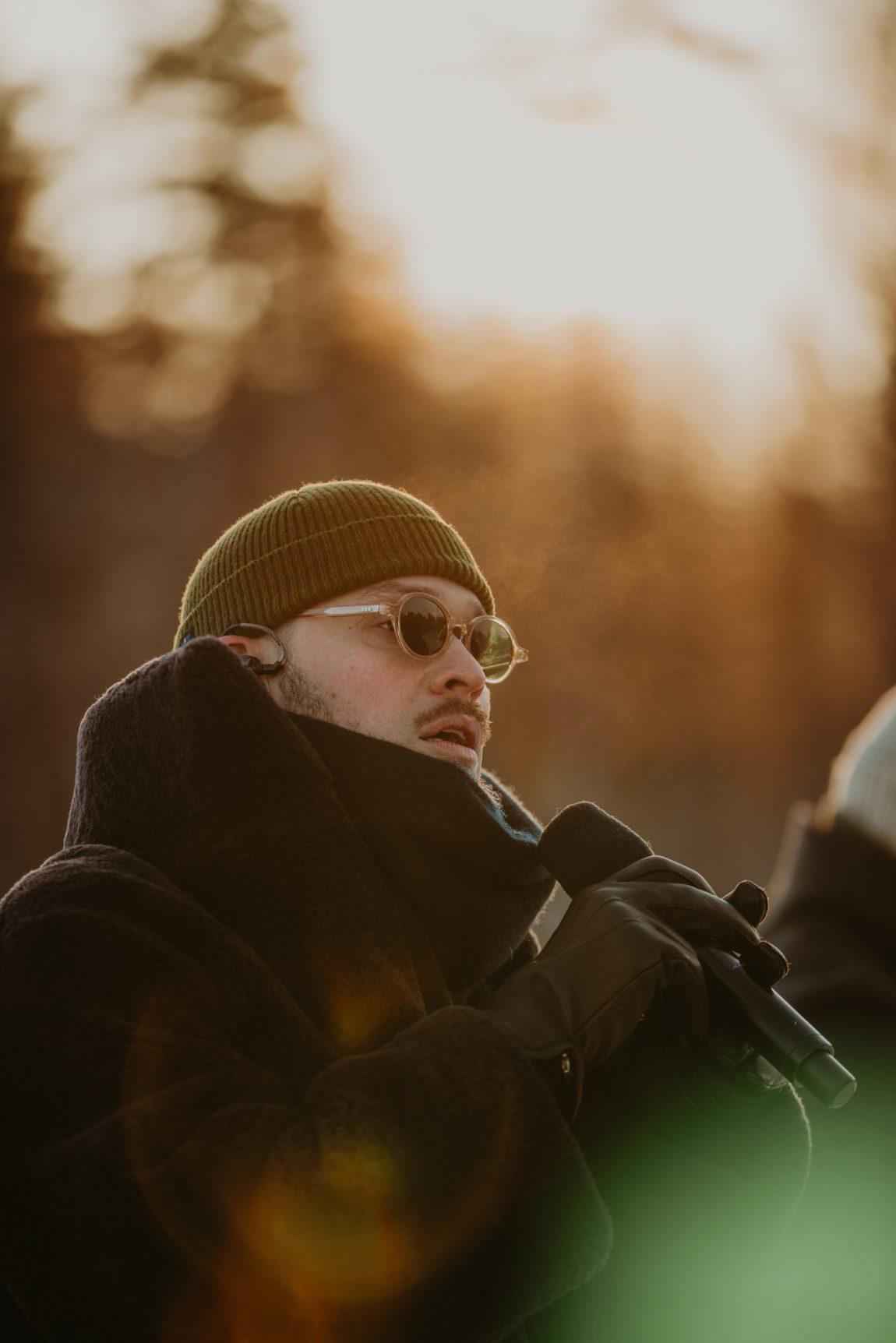 Nært av Stig Brenner som synger i skogen. Man ser ham i profil der han holder mikrofonen foran ansiktet. Han har trukket jakka godt oppunder haka og har skinnhansker på. På hodet har han en mørkegrønn lue og et par runde solbriller dekker øynene hans.