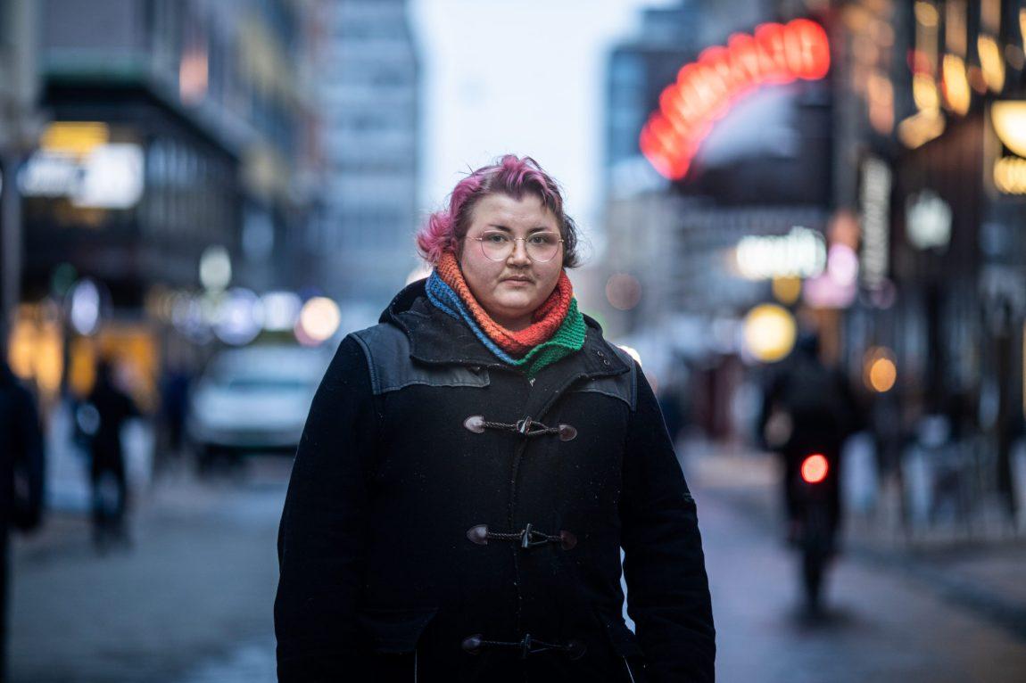 I Oslo-sentrum står Jane oppstilt for et portrett. Iført en svart jakke, en krage i blått, oransje og grønt, og med lillafarget hår. Bakgrunnen er uklar. Jane stirrer rett i kameraet.