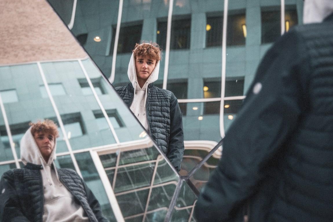 Jonas Tidemann står foran en glassvegg som speiler ham fra flere vinkler. Han har den grå hettegenseren trukket over hodet og en svart quiltet jakke er åpen. Mørke krøller ligger ned i panna og han ser rett fra mot kameraet.