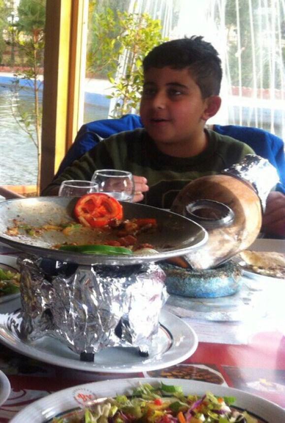 En ung, bollekinnet sitter ved middagsbordet og smiler. Foran ham er det en hel haug med mat som skal nytes. I bakgrunn ser vi en fontene.