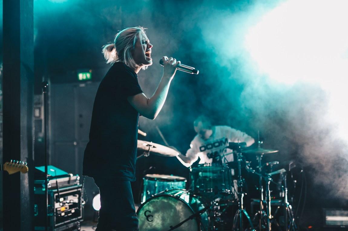 Helene står på scenen med en stor svart t-skjorte og dongeribukser på seg. Hun synger med mye innlevelse inn i mikrofonen. I Bakgrunnen ser vi Johan som spiller på trommer og røyk fra en røykmaskin.
