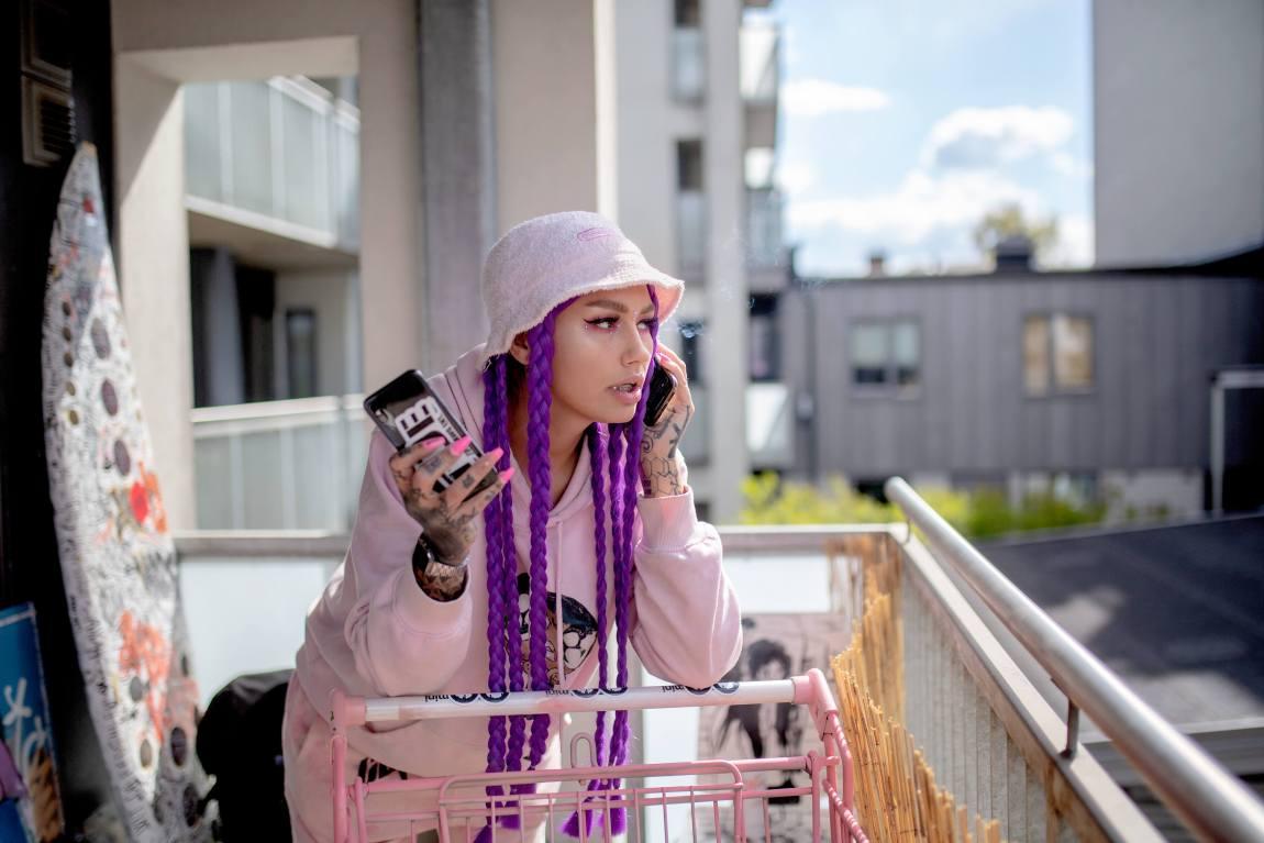 En røykende Helene på balkongen later som hun snakker i telefonen.