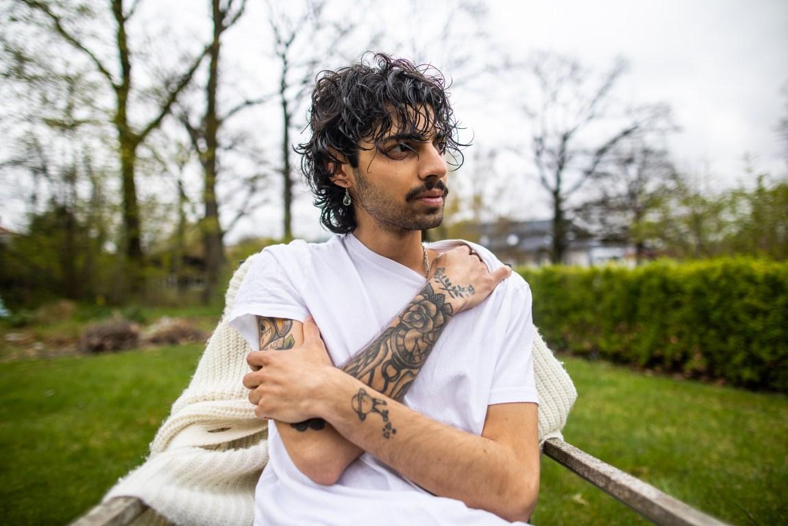 Med armene i kryss, sitter den unge mannen på en stol i en park. Han har armene i kryss og holder seg fast. Han ser kald og trøtt ut.